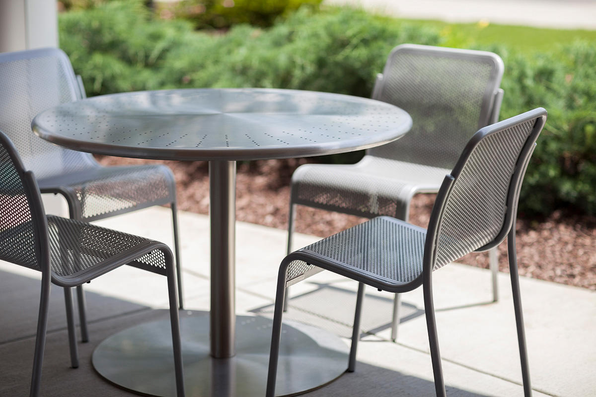 "Column Table shown with 42"" round perforated table top in Stainless Steel"