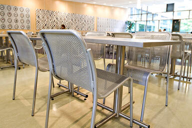 Cross Tables shown with square Sandstone Stainless Steel table tops