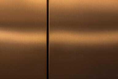 Elevator doors shown in Fused Bronze with Satin finish and custom Eco-Etch patte