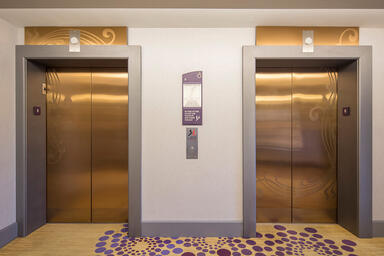 Elevator doors and transoms shown in Fused Bronze with Satin finish
