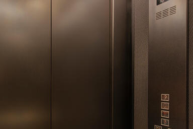 Elevator doors in Fused Nickel Silver and Sandstone finish; LEVELe-105 Elevator