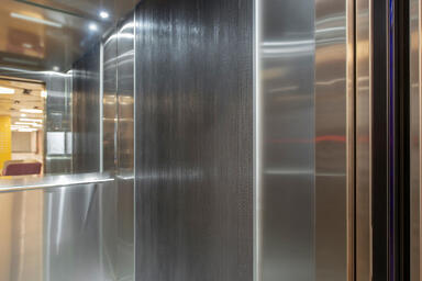 Elevator interior with panel in Bonded Aluminum with Natural Patina