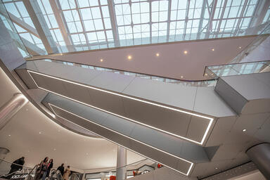 Escalator truss cladding in ViviChrome Chromis glass with custom color interlaye