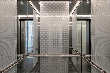 Elevator interior panels with ViviStrata Layers glass in Reflect configuration w