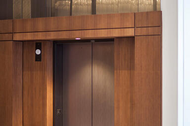 Elevator doors in Fused Nickel Bronze with Satin finish and Silkworm Eco-Etch