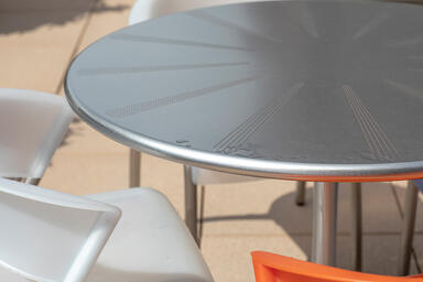 "Citrus Table shown with 42"" table top in Stainless Steel with Sandstone finish a"