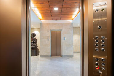 Return walls in Fused Nickel Bronze with Seastone finish; elevator doors in Fuse